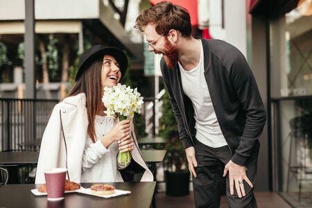 Happy woman receiving bouquet from boyfriend