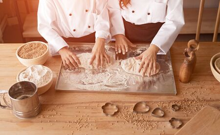 Children in cook uniform kneading dough on metal stand on table