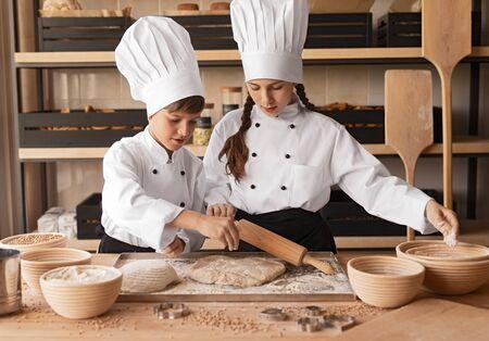 Little bakers preparing dough on table 版權商用圖片