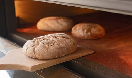 Fresh bread placed on wooden shovel near hot industrial oven in bakery