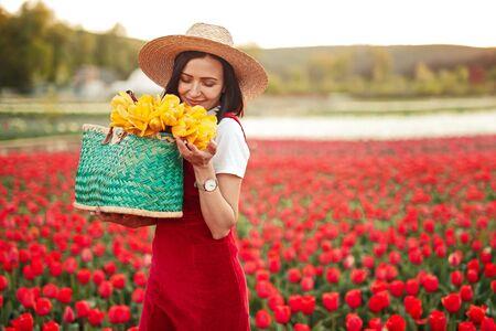 Happy woman smelling flowers in field 版權商用圖片