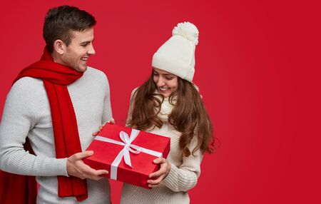 Happy man giving Christmas present to girlfriend