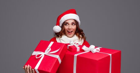 Amazed woman with bunch of Christmas gifts