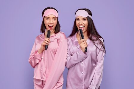 Excited ladies in pajamas singing into combs