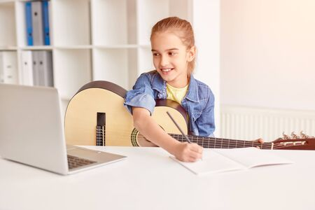 Cheerful child making notes during online guitar lesson