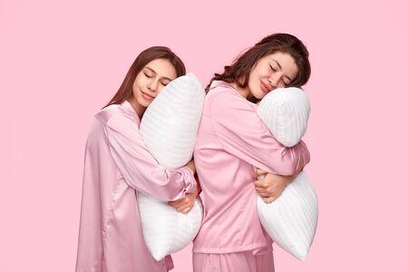 Best friends hugging pillows and sleeping