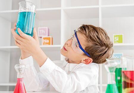 Thoughtful little chemist examining liquid