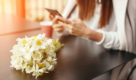 Bouquet placed on table near anonymous woman during date Stock fotó