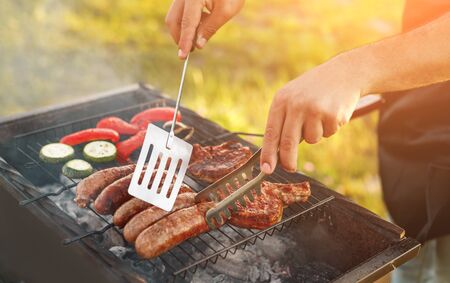 Crop chef turning sausages on grill