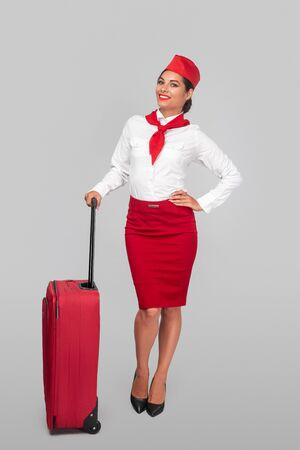Friendly stewardess with suitcase before flight