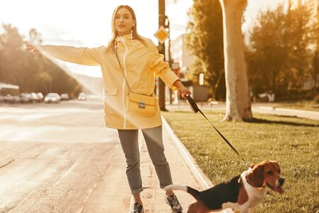 Woman catching car on road with dog on leash