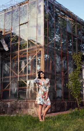 Graceful woman in dress on background of greenhouse building