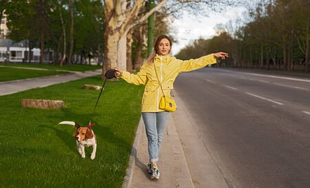 Active woman getting car on road with dog on leash on grass