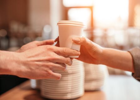 Anonymous client taking beverage from barista
