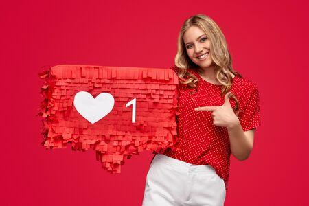 Cheerful female influencer on red background Foto de archivo
