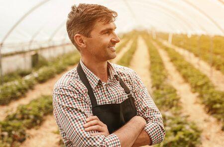 Confident farmer in modern greenhouse