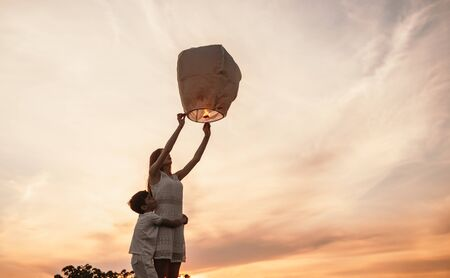 From below side view of little boy embracing teen sister while girl releasing sky lantern and together making wish, standing against sunset sky in summer evening Stock fotó