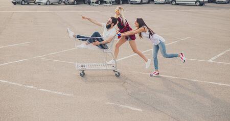 Frauen schieben Einkaufswagen mit männlichem Freund