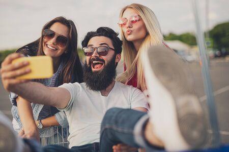Bearded man taking selfie with women during shopping