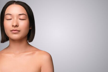 Chinese woman with closed eyes near empty space