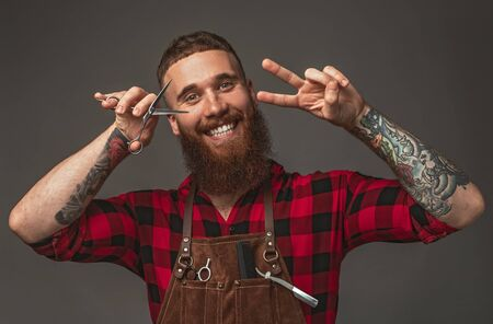 Cheerful barber with scissors gesturing V sign
