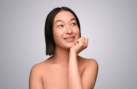 Dreamy Chinese female thinking about skincare