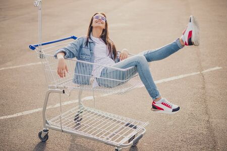 Cheerful woman in shopping cart swinging legs 写真素材