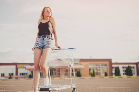 Stylish woman leaning on shopping cart