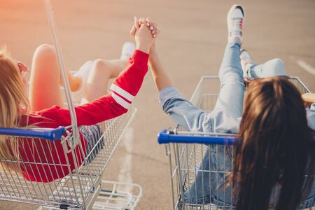 Anonymous best friends holding hands and riding shopping trolleys