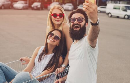 Cheerful friends with shopping trolley taking selfie