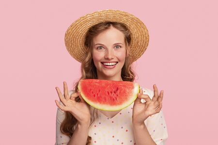 Excited young woman with piece of watermelon