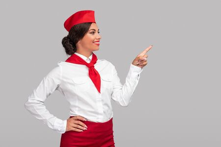 Cheerful ethnic stewardess pointing at empty space