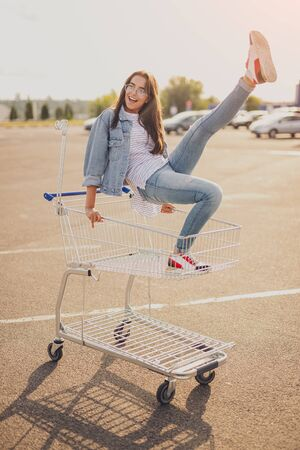 Excited young lady having fun on shopping trolley 写真素材