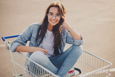 Ethnic female sitting in shopping trolley