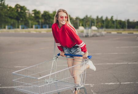 Joyful woman with shopping cart standing on parking 写真素材