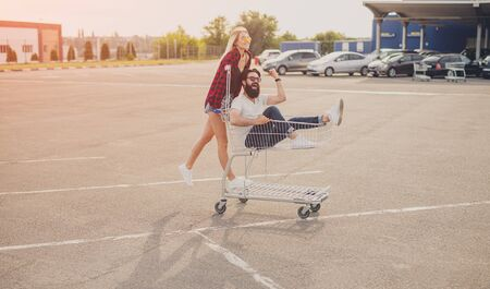 Crazy couple riding shopping trolley 写真素材