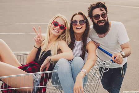 Crazy young friends with shopping cart