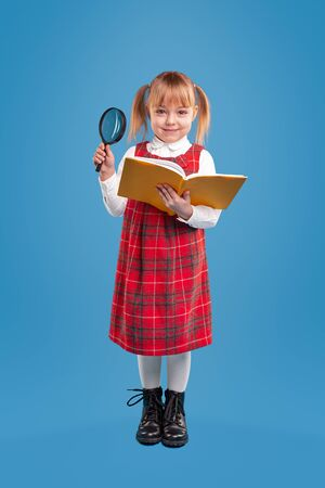Little girl with book and magnifier