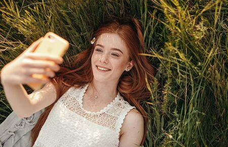 Happy young woman taking selfie on grass