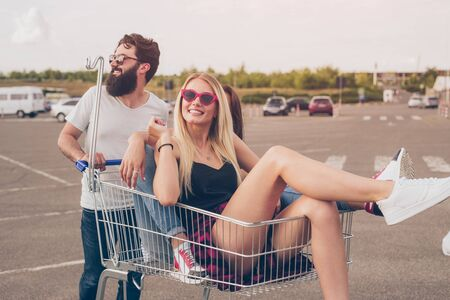 Man pushing shopping trolley with female friends