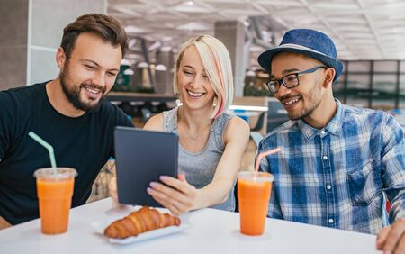 Cheerful diverse friends using tablet during lunch in cafe