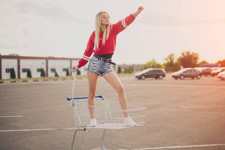 Confident young woman standing in shopping trolley 写真素材