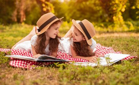 Cheerful sisters reading books during picnic