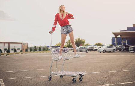 Stylish woman standing in shopping trolley on parking lot 写真素材