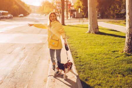 Woman with dog catching cab on roadside