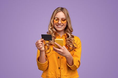 Happy woman with bank card shopping via smartphone