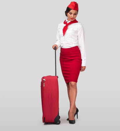 Stylish Hispanic air hostess with luggage