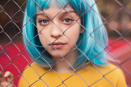 Teen girl with blue hair behind fence