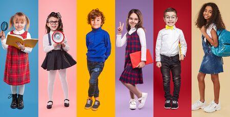 Diverse little schoolgirls and schoolboys against vibrant background in studio