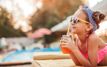 Happy little girl with orange juice relaxing at poolside in sunny summer day